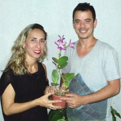 Luiz recebe a orquídea das mãos da vice-presidente da ACEO, Juliana Coelho
